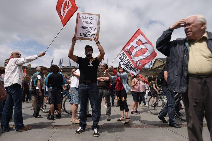 Un manifestant, la bouche recouverte par du scotch, brandit un panneau contre la loi Travail, mardi 5 juillet 2016 à Bordeaux (Aquitaine). (NICOLAS TUCAT / AFP)