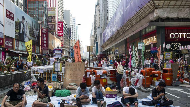 Des manifestants pro-démocratie sont assis devant une barricade, le 6 octobre 2014, dans le centre de Hong Kong. (XAUME OLLEROS / AFP)