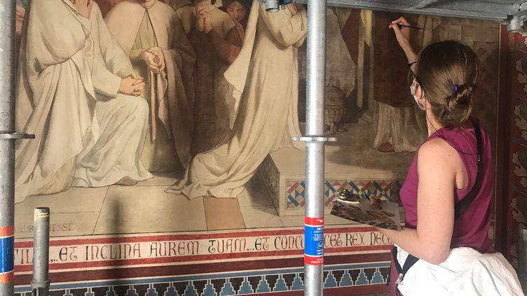 Une restauratrice, pinceau à la main, s'applique dans la chapelle Sainte-Geneviève,dans l'église Saint Séverin à Paris. (LOU BOURDY / RADIO FRANCE)