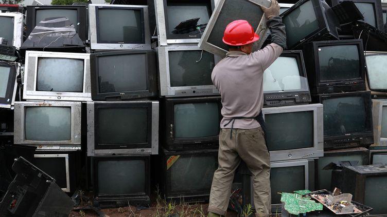 Un travailleur trie des vieux téléviseurs usagés, en attente de recyclage, le 30 mai 2013, à Neijang, en Chine. (LIU AIGUO / IMAGECHINA / AFP)