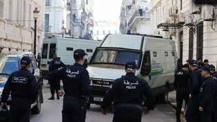 Des policiers devant le véhicule qui a amené les deux ex-Premiers ministres alégiens à leur procès à Alger, le 2 décembre 2019. (BILLAL BENSALEM / AFP)