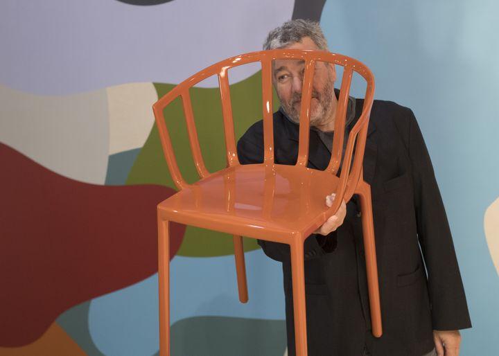 Le designer Philippe Starck montre une des chaises réalisées pour Kartell au Salon du meuble de Milan, le 4 avril 2017  (MIGUEL MEDINA / AFP)
