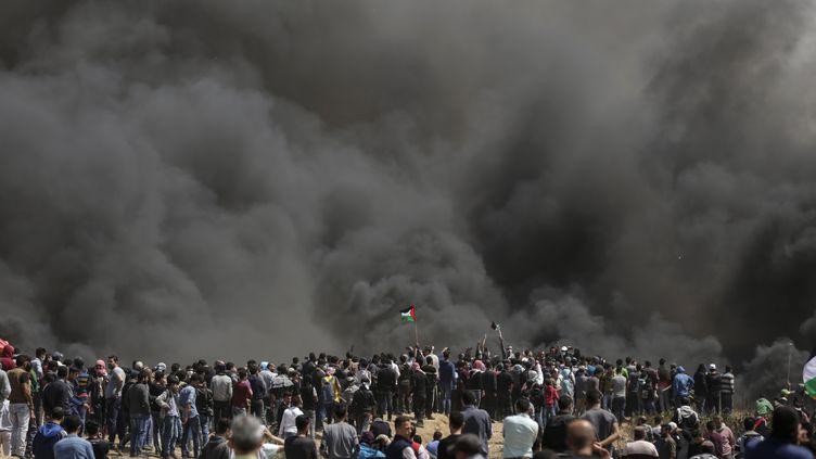 Des Palestiniens rassemblés derrière la fumée de pneus brûlés, vendredi 6 avril 2018 à la frontière entre Israël et la bande de Gaza. (MAHMUD HAMS / AFP)