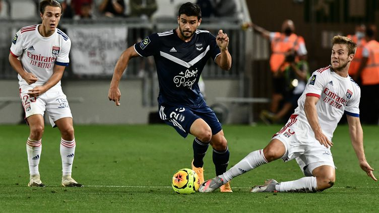 Loris Benito, joueurs des Girondins de Bordeaux, à la lutte avec Joachim Andersen de l'OL. (PHILIPPE LOPEZ / AFP)