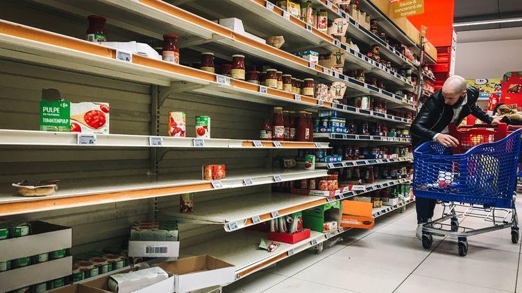 Un client d'un supermarché de Villeneuve-la-Garenne (Hauts-de-Seine) fait face à des rayons partiellement vides, le 2 mars 2020, lors de l'épidémie de coronavirus Covid-19. (AFP)