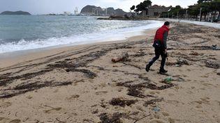 Un homme marche sur la plage de La Ciotat(Bouches-du-Rhône) polluée par des boulettes d'hydrocarbure, le 1er novembre 2018. (GERARD JULIEN / AFP)