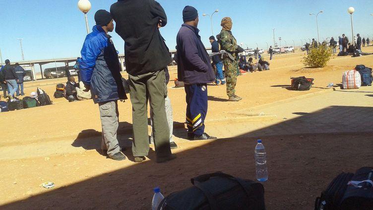 Des travailleurs algériens entourent un terroriste armé, à In Amenas, mercredi 16 janvier. (KYODO / REUTERS)