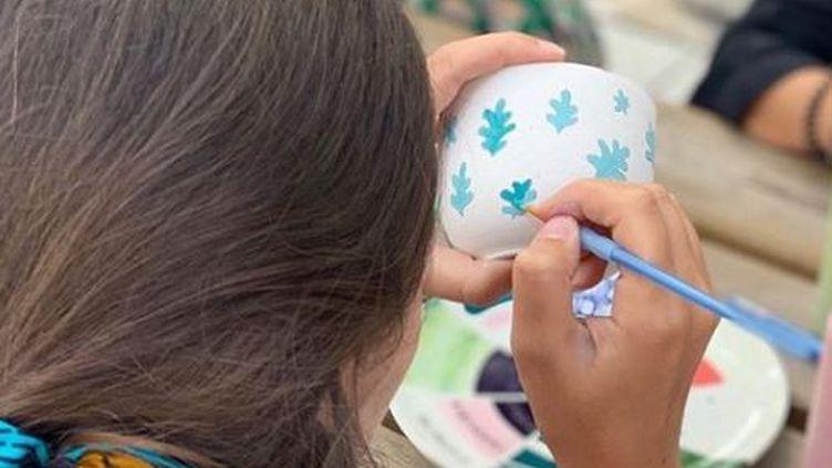 Une femme peint un bol. (lateliergenevieve)