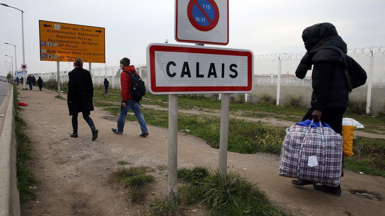 """Un migrant transporte ses affaires, lors du démantèlement de la """"jungle"""" de Calais, le 23 octobre 2016. (PASCAL ROSSIGNOL / REUTERS)"""