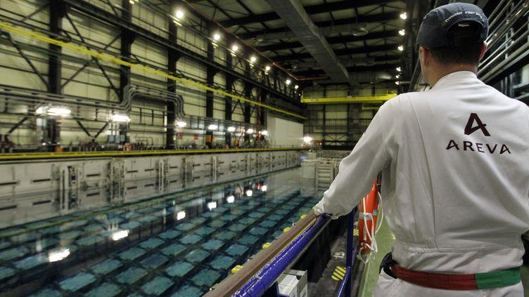 Un salarié d'Areva devant une piscine de refroidissement de l'usine de la Hague (Manche), le 22 novembre 2011. (KENZO TRIBOUILLARD / AFP)