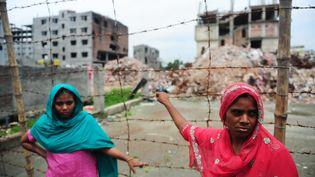 Deux ouvrières textiles devant le bâtiment effondré dans lequelelles travaillaient à Dacca, au Bangladesh, le 24 juin 2013. (MUNIR UZ ZAMAN / AFP)