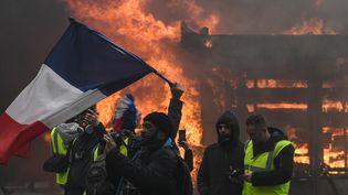 """Des """"gilets jaunes"""" manifestent à Paris sur les Champs-Elysées, le samedi 16 mars. (ALAIN JOCARD / AFP)"""