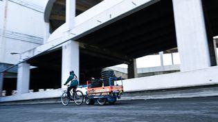 Un cycliste avec une remorque fournie par K-Ryole transporte un chargement. (K-Ryole)