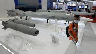 Un homme marche parmi des missiles de croisière supersoniques lors du 13e Salon international de l'aviation et de l'aérospatiale de Chine à Zhuhai, dans la province du Guangdong (sud de la Chine), le 28 septembre 2021. (NOEL CELIS / AFP)