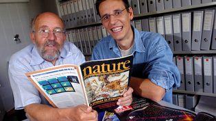 """Michel Mayor et Didier Queloz, avec le numéro de """"Nature"""" dans lequel a été publié leur article, le 11 août 2005, à l'université de Genève. (MAXPPP)"""