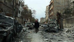 Un homme marche dans une rue de Douma dans la Ghouta orientale (Syrie), le 25 février 2018. (HAMZA AL-AJWEH / AFP)