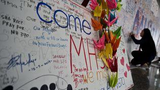 Une Malaisienne écrit un message sur un mur de l'aéroport de Kuala Lumpur (Malaisie), le 17 mars 2014, en hommage aux disparus du vol MH 370 deMalaysia Airlines. (MANAN VATSYAYANA / AFP)