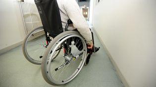 Un handicapé en fauteil roulant dans un couloir sur son lieu de travail. (MAXPPP)