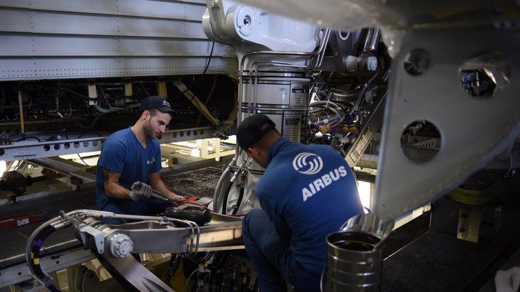 Des techniciens d'Airbus installent un train d'atterrissage sur un A380, à Blagnac (Haute-Garonne), le 22 avril 2016. (REMY GABALDA / AFP)