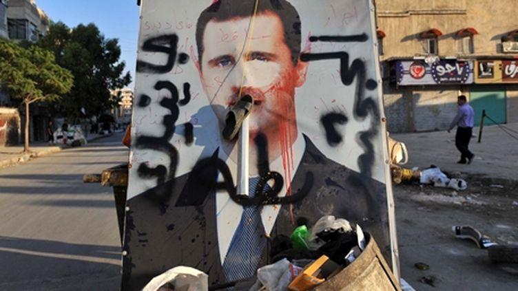 Affiche vandalisée du président Syrien Assad sur un tas de déchets à Alep (nord de la Syrie), le 24 juillet 2012. (AFP - BULENT KILIC)