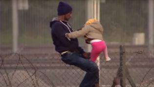 Une petite fille de 3 ans escalade avec l'aide d'un adulte une barrière à Calais (Pas-de-Calais), dans une vidéo diffusée par les médias britanniques en juillet 2015. (DAILY MIRROR / YOUTUBE)