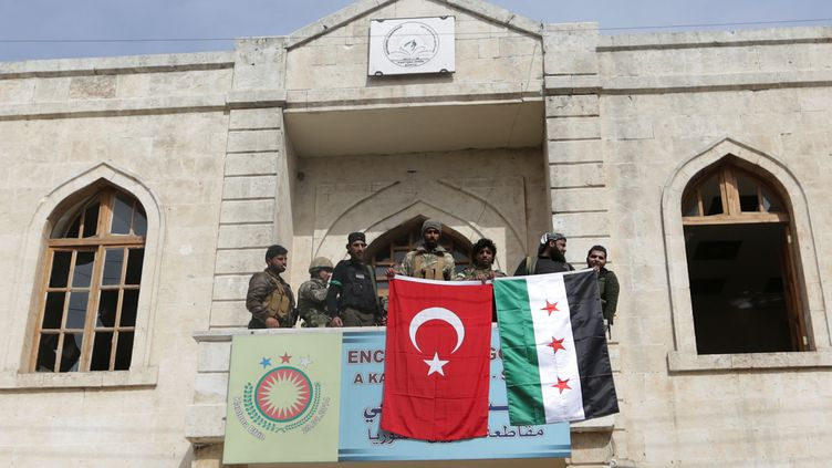 Des combattants affichent les drapeaux turc et syrien à Afrine (Syrie), le 18 mars 2018. (KHALIL ASHAWI / X03676)