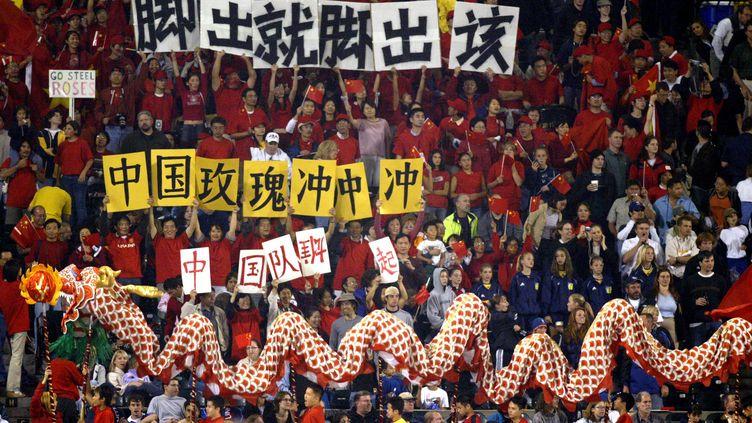 Les supporters chinois encouragent leur équipe nationale lors de son quart de finale de Coupe du monde féminine contre le Canada, le 2 octobre 2003 à Portland (Etats-Unis). (TOM HAUCK / GETTY IMAGES NORTH AMERICA)