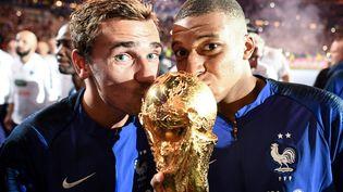 Antoine Griezmann (à gauche) et Kylian Mbappé embrassent le trophée qui récompense les vainqueurs de la Coupe du monde, le 9 septembre 2018 au Stade de France (Seine-Saint-Denis). (FRANCK FIFE / AFP)