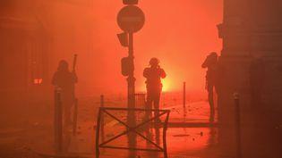 """Un policier fait face à un incendie déclenché en plein cœur de Paris lors de la manifestation des """"giles jaunes"""", samedi 1er décembre 2018. (LUCAS BARIOULET / AFP)"""