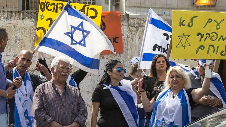 Des Israéliens défendant le soldat Azaria affichent les couleurs nationales à l'entrée de la salle où se tient le procès du soldat accusé d'avoir tué un Palestinien. (JACK GUEZ / AFP)