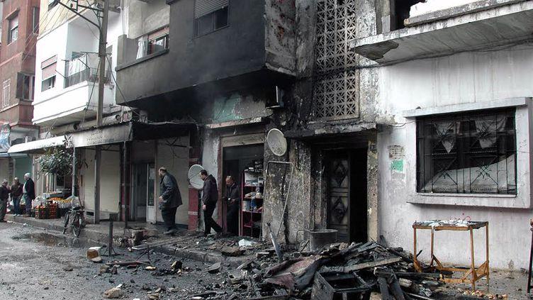 Dégâts causés par une attaque au mortier attribuée à l'opposition syrienne, dans une rue de Homs, le 9 janvier 2014. (HO / AFP)