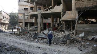 Une Syrienne devant les ruines d'un hôpital bombardé par le régime syrien dans la Ghouta orientale, le 21 février 2018. (ABDULMONAM EASSA / AFP)