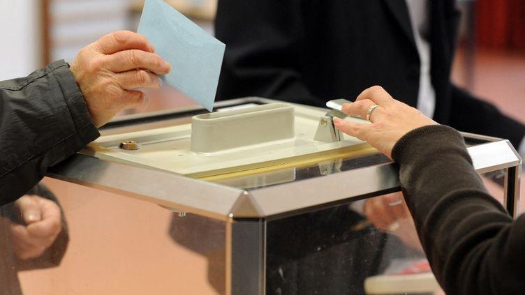 Un électeur glisse son bulletin dans l'urne, lors des élections régionales, le 13 décembre 2015 à Quintin (Côtes-d'Armor). (FRED TANNEAU / AFP)