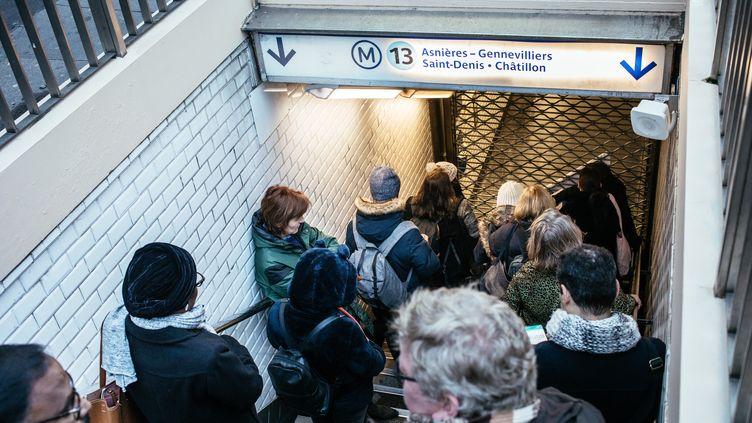 Des passagers du métro parisien devant une grille fermée d'une station de la ligne 13 du métro, le 2 janvier 2020. (MATHIEU MENARD / AFP)