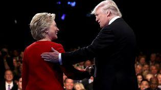 Donald Trump et hillary Clinton se serrent la main avant de s'affronter lors du premier débat de la présidentielle américaine, le 26 septembre 2016, à Hempstead. (JOE RAEDLE / REUTERS)