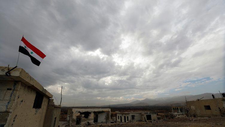 Un drapeau syrien sur le village de Beit Jann (Syrie) lors de l'évacuation de ses habitants, le 29 décembre 2017. (OMAR SANADIKI / REUTERS)
