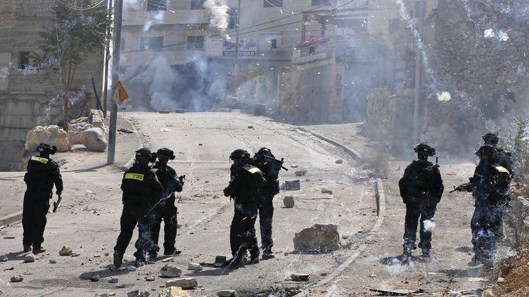Des policiers israéliens font face à des militants palestiniens dans l'est de Jérusalem, le 4 octobre 2015. (AMMAR AWAD / REUTERS)