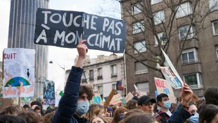 """Un jeune homme brandit une pancarte """"Touche pas à mon climat"""" dans une manifestation, à Paris, le 19 mars 2021. (MYRIAM TIRLER / HANS LUCAS / AFP)"""