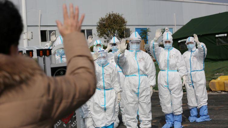 Des soignants disent au revoir à un patient guéri du Covid-19, le 1er mars 2020, à l'hôpital Leishenshan de Wuhan (Chine). (CHINA DAILY CDIC / REUTERS)
