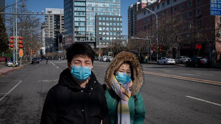 Un homme et une femme dans une rue de Pékin (Chine), le 15 février 2020 (photo d'illustration). (NICOLAS ASFOURI / AFP)