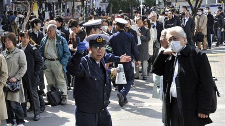 Habitants de Tokyo attendant des trains dans la capitale confrontée à des pannes de courant (14/03/2011) (AFP / Yoshikazu Tsuno)