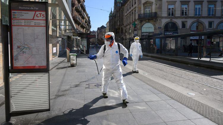 Des employés désinfectent le mobilier urbain du tramway à Strasbourg (Bas-Rhin), le 1er avril 2020. (PATRICK HERTZOG / AFP)