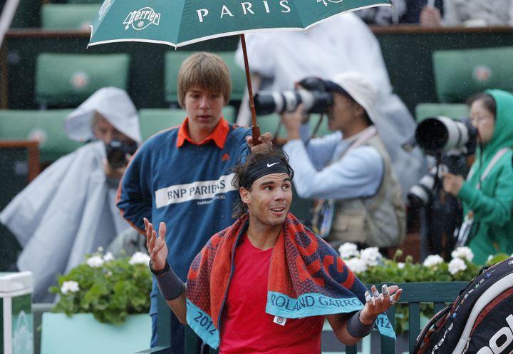 L'Espagnol Rafael Nadal sous la pluie à Roland-Garros le 11 juin 2012 à Paris. (GONZALO FUENTES / REUTERS)