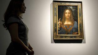 """Une employée de Christie's prend la pose devant le tableau de Leonard de Vinci, """"Salvator Mundi"""", le 22 octobre 2017 à New York (Etats-Unis). (TOLGA AKMEN / AFP)"""