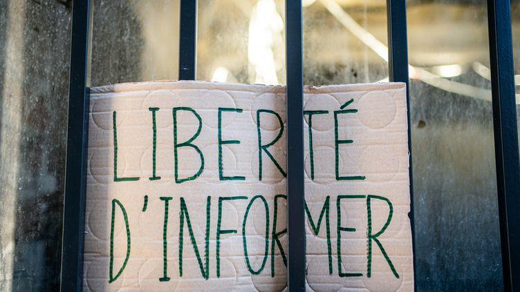"""Une pancarte dans une vitrine pour protestercontre le projet de loi sur la """"sécurité globale"""", à Paris,le 18 novembre 2020. (XOSE BOUZAS / HANS LUCAS / AFP)"""