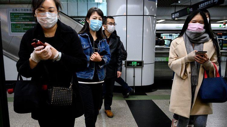 Des Chinoises dans le métro, à Shangai, le 23 mars 2020. (NOEL CELIS / AFP)