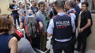 Des policiers catalans discutent avec des indépendantistes présents dans une école dans le quartier de barcelonais de Garcia (Espagne), le 30 septembre 2017. (JOSEP LAGO / AFP)