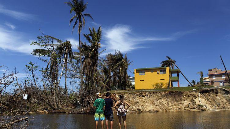 Des personnes regardent les dégâts causés par l'ouragan Maria à Porto Rico, le 6 octobre 2017. (RICARDO ARDUENGO / AFP)