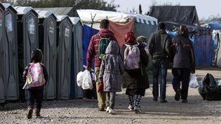 """Une famille afghane marche dans la """"jungle"""" à Calais (Pas-de-Calais), dimanche 23 octobre, à la veille du démantèlement du camp. (ETIENNE LAURENT / EPA)"""
