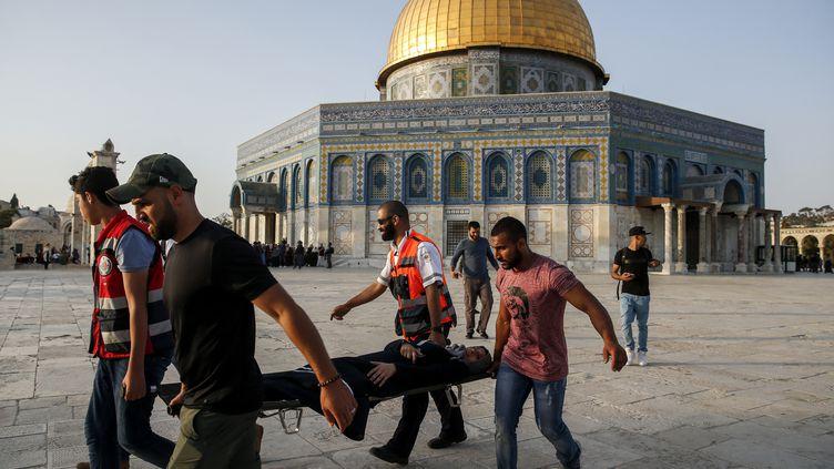 Des Palestiniens transportent une femme blessée sur l'esplanade des Mosquées àJérusalem, le 27 juillet 2017. (AHMAD GHARABLI / AFP)
